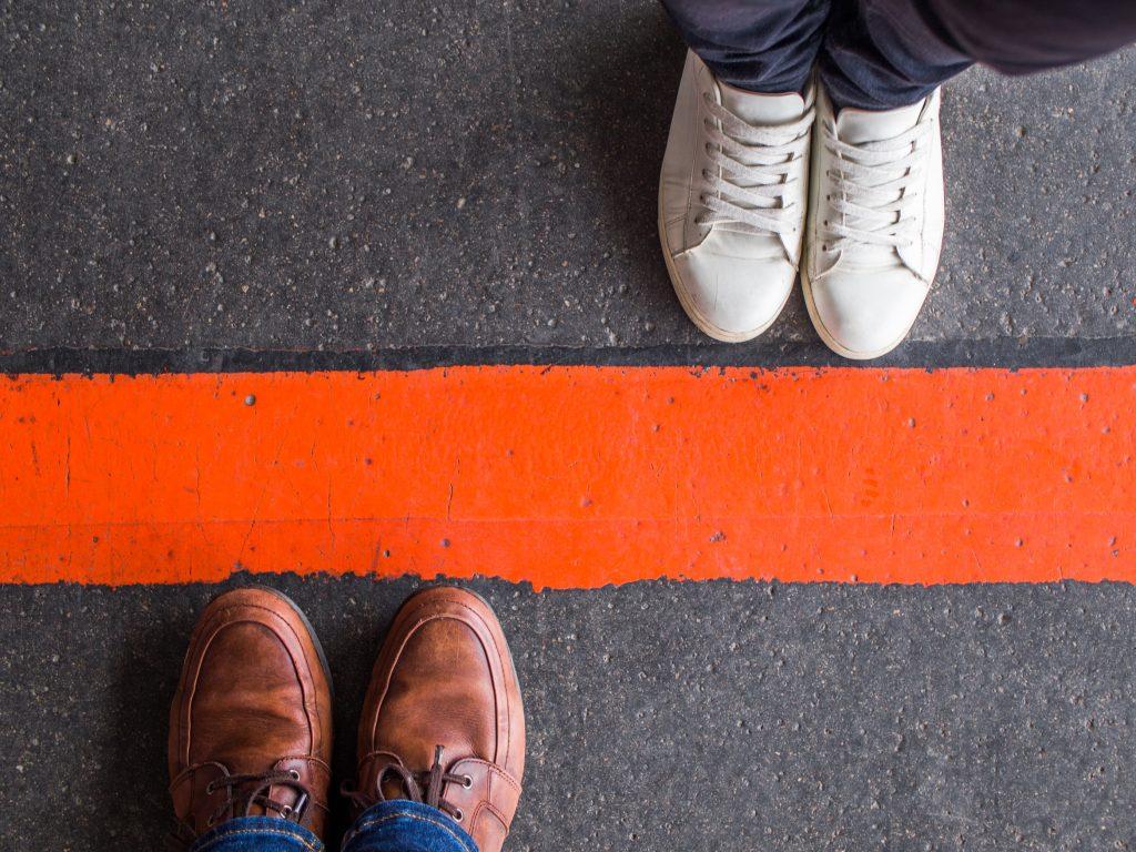 Roter Strich auf der Straße, der Frauen- und Männerschuhe trennt