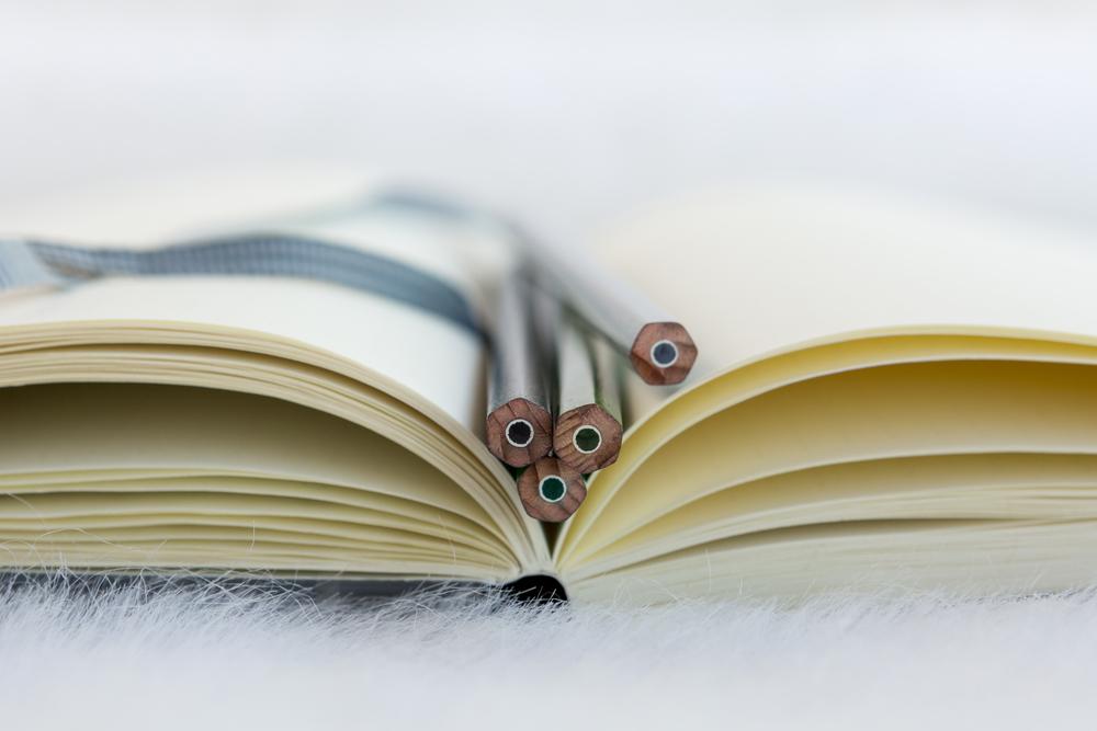 Offenes Buch mit leeren Seiten und 4 Stiften darin