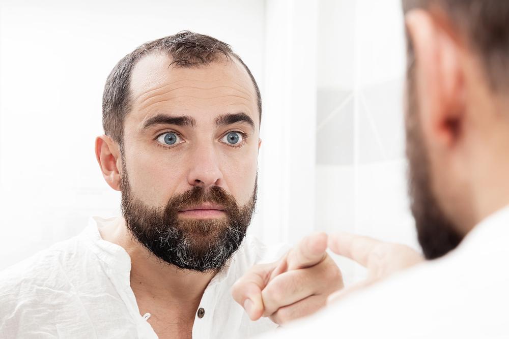 Mann mit Bart schaut sich im Spielgel an